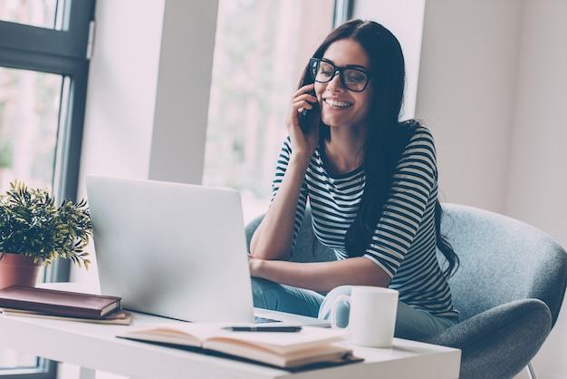 항상 연락합니다. 작업장에 앉아 노트북 작업을 하고 휴대전화로 통화하는 쾌활한 젊은 미녀