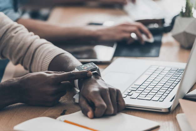 항상 연락합니다. 책상에 앉아 팀과 함께 일하는 동안 스마트 시계를 설정하는 아프리카 남자의 클로즈업