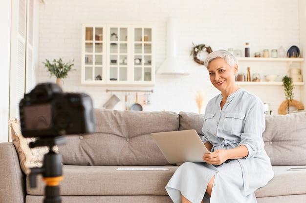 항상 연락합니다. 무릎에 휴대용 컴퓨터와 함께 소파에 앉아 파란 드레스를 입고 세련된 우아한 자영업자 수석 여성, 블로그 용 비디오 녹화, 비즈니스 비밀 말하기, 흥분된 모습
