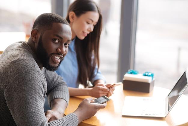 常に連絡を取り合う。ハンサムな若い男は、彼の女性の友人と窓の近くのテーブルに座っている間、笑顔で新しいスマートフォンを穴をあけます。