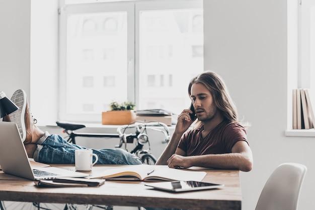 Всегда на связи. красивый молодой человек с длинными волосами разговаривает по мобильному телефону, сидя на своем рабочем месте в офисе