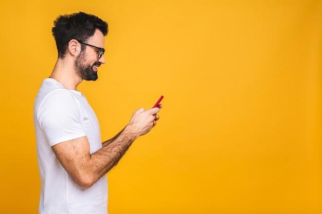 Всегда на связи. счастливый молодой человек в очках, набрав sms, изолированные на желтом фоне, улыбаясь и глядя на камеру.