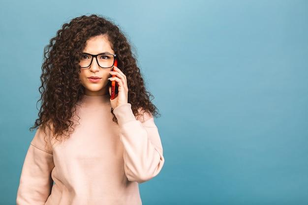 Всегда на связи! портрет разъяренной курчавой молодой женщины разговаривает по мобильному телефону, изолированному на синем фоне.