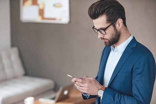 Всегда на связи. вид сбоку красивого молодого человека в очках, держащего смартфон и смотрящего на него, стоя в офисе