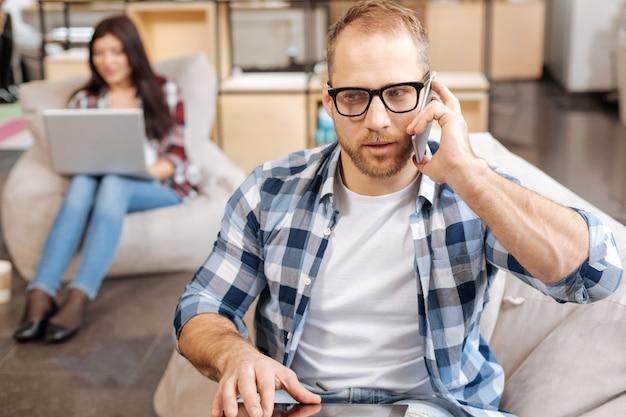 Всегда на связи. умный красивый уверенный в себе мужчина сидит в офисе и разговаривает по телефону во время обсуждения рабочих вопросов