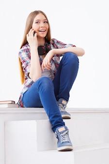 Всегда на связи с друзьями. милая девочка-подросток разговаривает по мобильному телефону и улыбается, сидя на лестнице