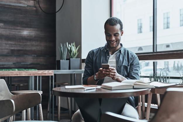 Всегда на связи с друзьями. красивый молодой африканец с помощью своего смартфона