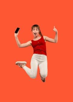 Sempre sul cellulare. integrale della donna abbastanza giovane che prende il telefono mentre salta contro il fondo rosso dello studio. mobile, movimento, movimento, concetti aziendali