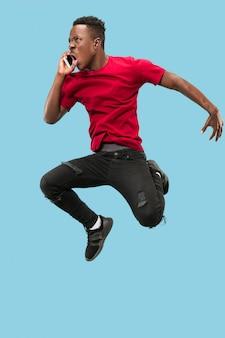 항상 모바일. 파란색 스튜디오 배경에서 점프하는 동안 전화를 받는 잘생긴 아프리카 청년의 전체 길이입니다. 모바일, 모션, 운동, 비즈니스 개념