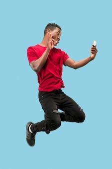 항상 모바일. 점프하는 동안 전화를 복용 잘 생긴 젊은 남자의 전체 길이