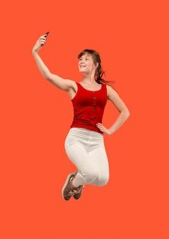常にモバイルで。赤いスタジオの背景にジャンプしながら電話を取り、自分撮りを作るかなり若い女性の完全な長さ。モバイル、モーション、動き、ビジネスコンセプト