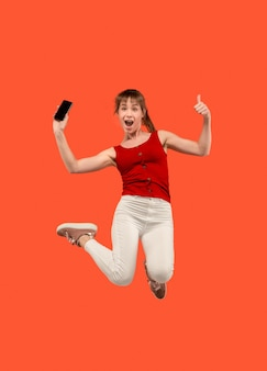 常にモバイルで。赤いスタジオの背景にジャンプしながら電話を取るかなり若い女性の完全な長さ。モバイル、モーション、動き、ビジネスコンセプト