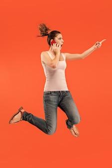 常にモバイルで。赤いスタジオの背景にジャンプしながら電話を取るかなり若い女性の完全な長さ。