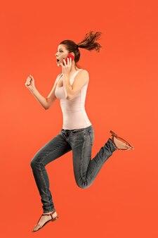 Всегда на мобильном телефоне. полная длина довольно молодой женщины принимая телефон, прыгая на красном фоне студии.
