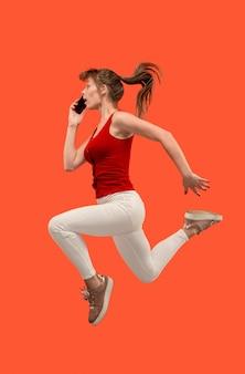 Всегда на мобильном телефоне. полная длина довольно молодой женщины принимая телефон, прыгая против красной студии.