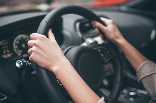 항상 이동 중입니다. 자동차를 운전하는 동안 핸들에 여성 손의 클로즈업