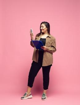 항상 온라인 인플루언서 분홍색 배경에 평상복을 입은 젊은 여성