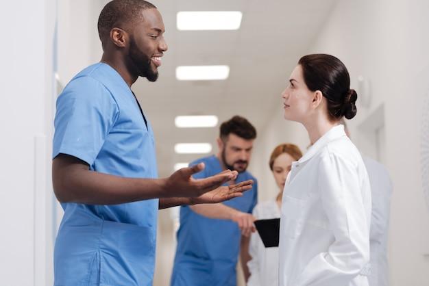常に他の意見を受け入れます。病院でコーヒーブレイクを楽しんだり、アイデアを共有しながら積極性を表現したりする、熟練した魅力的な施術者の笑顔