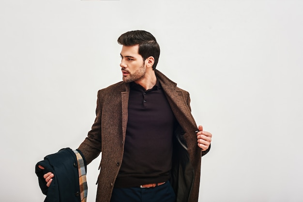 Always perfect stylish darkhaired man standing holding his coat and looking away isolated over white
