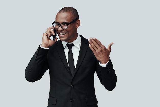 항상 도울 준비가 되어 있습니다. 정장 차림의 매력적인 젊은 아프리카 남자는 스마트 폰으로 통화하고 회색 배경에 서서 웃고 있습니다.