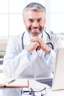 항상 도울 준비가 되어 있습니다. 자신의 작업장에 앉아 있는 동안 얼굴을 손에 기대고 웃고 있는 자신감 있는 성숙한 회색 머리 의사
