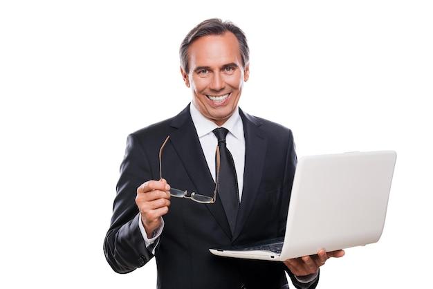 Всегда готов вам помочь. уверенный зрелый мужчина в строгой одежде держит ноутбук и улыбается, стоя на белом фоне