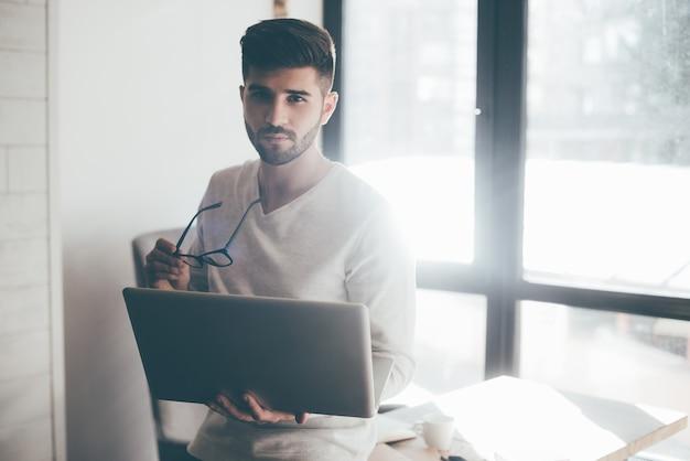 いつでもあなたを助ける準備ができています。オフィスの机に寄りかかってカメラを見ながらノートパソコンと眼鏡を持って自信を持って若い男