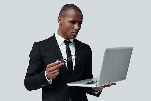 항상 도울 준비가 되어 있습니다. 회색 배경에 서 있는 동안 컴퓨터를 사용하여 작업하는 formalwear에서 젊은 아프리카 남자