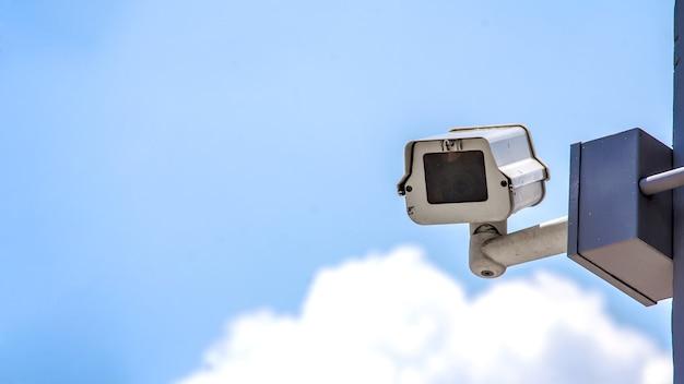 Всегда регистрируйте безопасность с камерой видеонаблюдения и голубым небом, белыми облаками длинного баннера Premium Фотографии