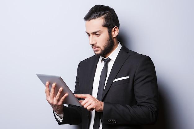 Всегда серьезно во время работы. уверенный молодой человек в формальной одежде работает над цифровым планшетом, стоя на сером фоне