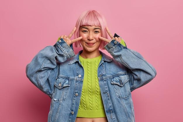 常に明るいままです。ポジティブな楽観的な女性は、目の上に平和の兆候を示し、ポジティブな雰囲気をあなたに送り、緑のセーターを着て、デニムジャケットは夏休みの幸せと喜びを表現します
