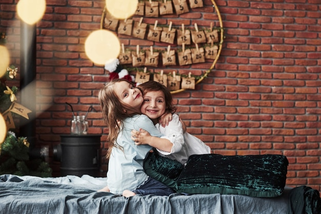 Always together. little girls having fun on the bed with holiday interior at the background