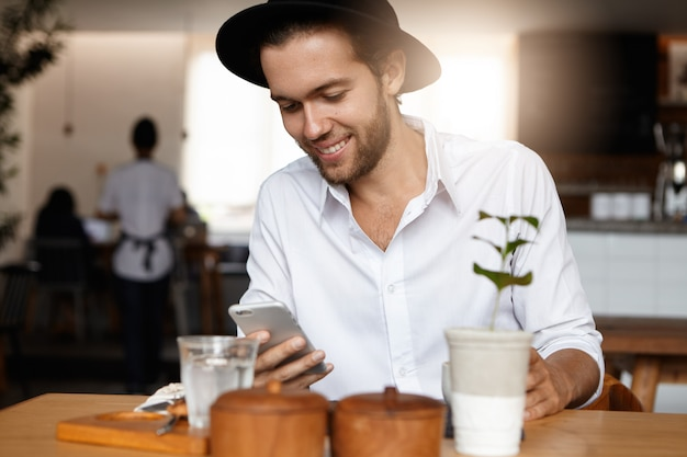 Always in touch. good-looking stylish young hipster typing sms to his girlfriend on his generic mobile phone, making appointment with her, using high speed internet connection at coffee shop