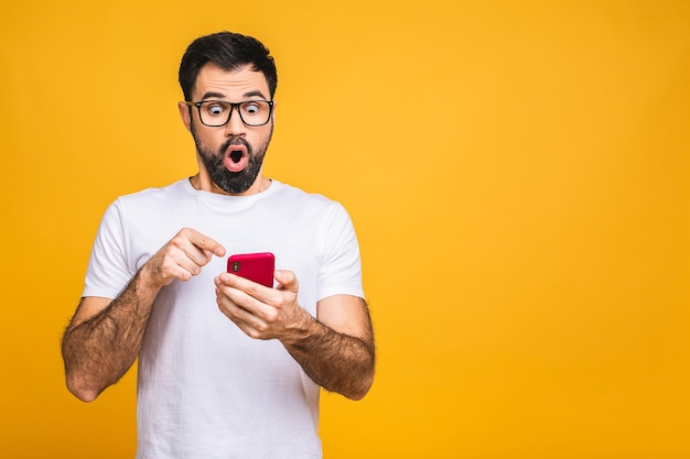 Always in touch. happy young amazed shocked bearded man in glasses typing sms on yellow background.