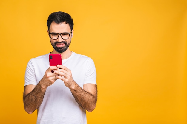 Always in touch. happy young man in glasses typing sms isolated on yellow background, smiling and looking at camera.