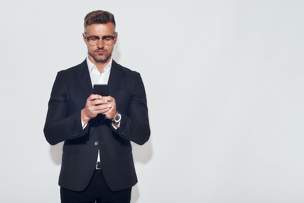 Always in touch. portrait of handsome bearded man in classic wear and eyeglasses holding smart phone and looking at it while standing against grey background. digital concept. business concept
