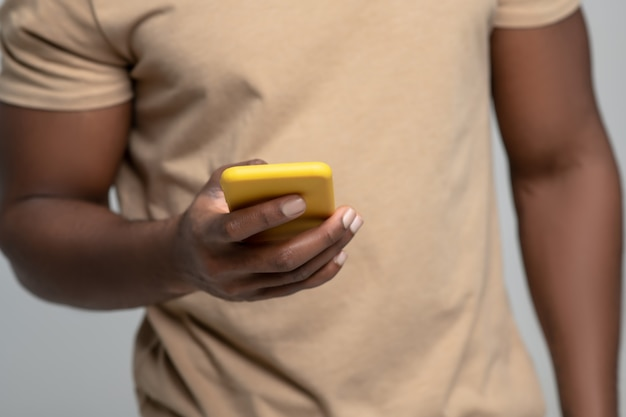 Always in touch. strong muscular black man hand holding yellow smartphone, face not visible