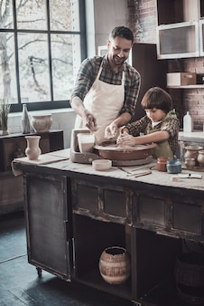 Всегда готов учиться у отца. веселый молодой человек и маленький мальчик делают керамический горшок на уроке гончарного дела