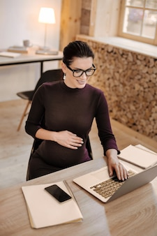 Всегда работаю. вид сверху брюнетки творческой беременной бизнес-леди, работающей на ноутбуке, сидя за столом и надевая очки