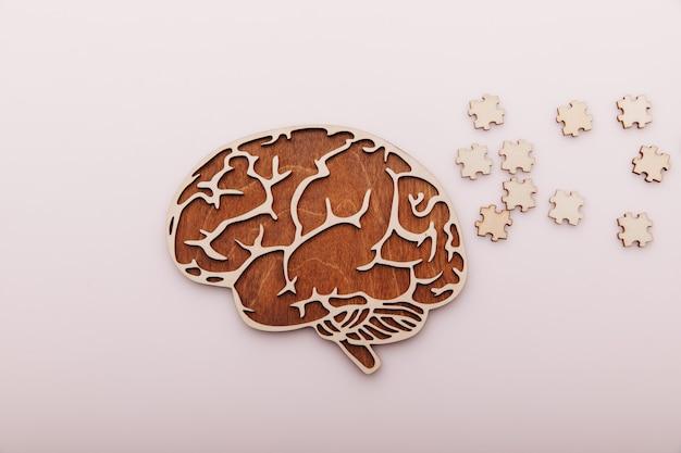 알츠하이머 병 및 정신 건강 개념. 책상에 두뇌와 나무 퍼즐.