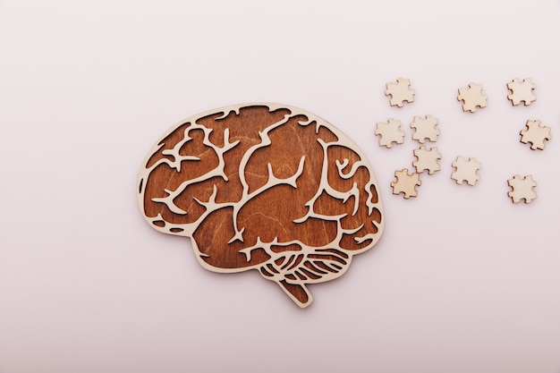 Alzheimer's disease and mental health concept. brain and wooden puzzle on a desk.