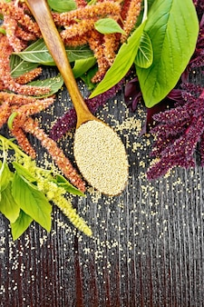 Amaranth groats in a spoon, red, burgundy and green inflorescences with leaves on the background of a wooden board from above