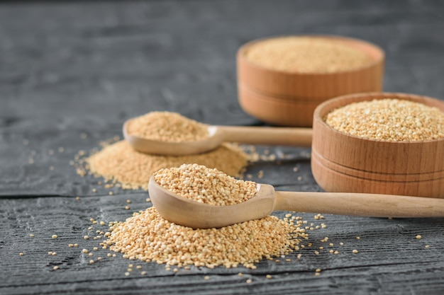 Amaranth and quinoa seeds and two wooden spoons on a table.