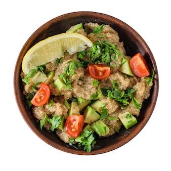 Салат семени амаранта с овощами в шаре глины изолированном на белизне. вид сверху.