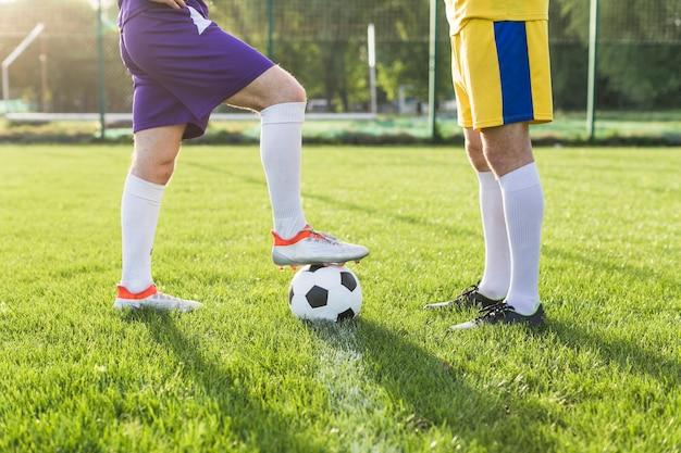 Concetto di calcio amatoriale con gambe di giocatori