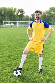 Amateur football concept with man posing with ball
