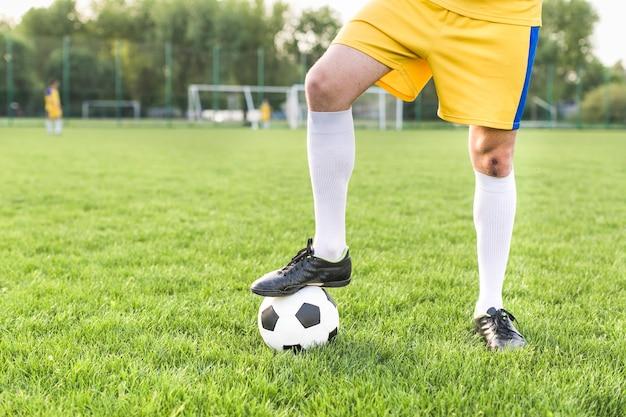 ボールでポーズをとる男とアマチュアフットボールのコンセプト