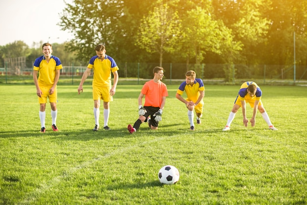 Amateur football concept with team stretching