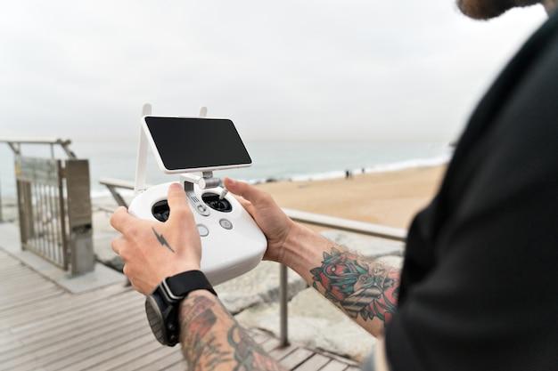 Фотограф-любитель или профессиональный фотограф или видеооператор настраивает съемочную площадку для съемки воздушного пейзажа океана с помощью дрона или квадрокоптера.