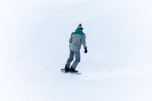 アマチュアスノーボーダーが山を転がり落ちる、リアビュー。スノーボードを持ったスポーツマンの背面図。ダブラー